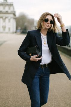 Emma Hill wearing navy check blazer, white t shirt, gold layered necklaces, round ray ban sunglasses, black belt, Chanel vintage timeless bag, dark wash levis 501 jeans