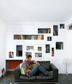 Mathieu Vinciguerra reads in front of his apartment's signature storyboard shelves.  Photo by Céline Clanet.