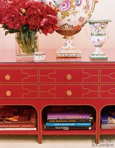 thefoodogatemyhomework:  A gold nailhead trimmed chest by interior designer Ernest de la Torre, covered in red horsehair, is topped with antique Meissen urns - faaaaabulous.