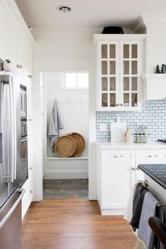 White kitchen glowing with blue mini brick backsplash tiles between white shaker cabinets and upper glass front China doors.