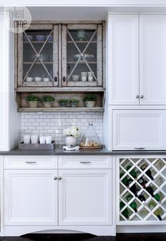 Kitchen cabinets: A kitchen bar area with weathered cabinets complete with built-in wine rack and beverage fridge
