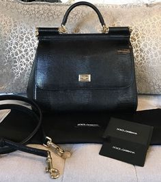 Stunning authentic Dolce & Gabbana Iguana Embossed Black Leather Miss Sicily Satchel Bag. Rare to get ahold of the iguana embossed leather! Gold tone hardware, single rolled top handle, magnetic snap closure flap (still has blue covered plastic on it) & flat optional shoulder strap. | eBay!
