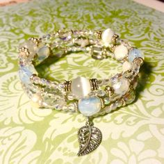 Crystal wrap bracelet with charm NWOT Fun wrap bracelet featuring Crystal Quartz,cat's eye, and Czech glass with silver plated accents. Sayre Jewelry Bracelets