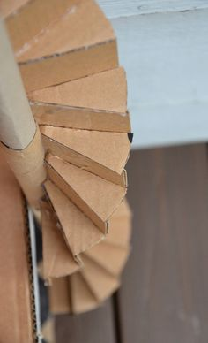 The steps were made from a single circle, cut into 16 segments, 8 (i.e. a semi-circle's worth) for each set of steps. The vertical pieces of the steps were rectangles, and each step was glued on in sequence, beginning from the bottom, to form the spiral. After the entire staircase was completed, it was glued to the side of the house.