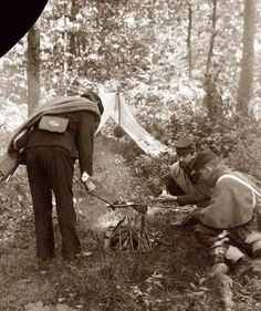 Soldiers at the battle of Gettysburg. Three men are seen cooking over a small campfire.