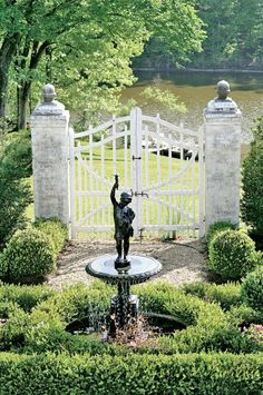 Camp Boxwoods garden with English boxwoods overlooking the pond. | Traditional Home