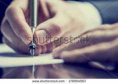 Retro effect faded and toned image of a man writing a note with a fountain pen. - stock photo