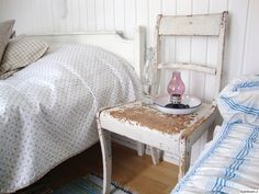 vanha tuoli,valkoinen,kulunut,tuoli,yöpöytä,kynttilälyhty,kynttilä,aitta,romanttinen,maalaisromanttinen,maalaisromanttinen sänky,makuuhuone,mökki,remontti,pilkullinen,rouhea,lasipullo,päiväpeite,päiväpeitto,maalaisromanttinen sisustus,kesäasunto,kakkosasunto