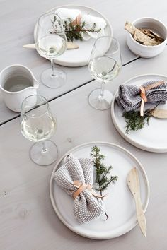 White and grey table setting with leather napkin-holders.