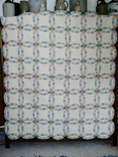 """A fantastic Double Wedding Ring quilt made of 1930's fabrics and finished in 1944.  The pieces are 1.5"""" in size and it is completely hand pieced and hand quilted.  The quilting is extremely good at 12-14 stitches per inch.  The backing is the same muslin fabric.  It appears that it has never been used or washed as the pencil lines for the quilting are still visible.  A great deal of thought & planning went into the quilt as fabric pieces were cut to center objects in the small pieces."""