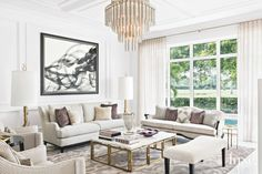 White Living Room with Glamorous Gold Fireplace and Chandelier | LuxeSource | Luxe Magazine - The Luxury Home Redefined