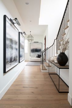Large art with picture lights above in the hallway with a glass cage chandelier . Large art with picture lights above in the hallway with a glass cage chandelier + iron stair railin Hallway Ideas Entrance Narrow, Entryway Ideas, Hallway Art, Flur Design, Hallway Designs, Modern Entryway, Foyer Decorating, My Dream Home, Home Interior Design