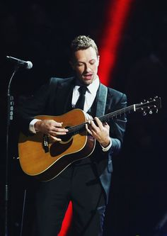 Chris Martin in a suit & guitar at 12-12-12 concert <3