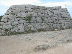 This is an image of Naveta des Tudons, in Menorca, Spain - A naveta is a megalithic chamber tomb unique to the Balearic island of Minorca. It dates to the early Bronze Age.