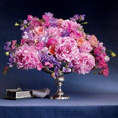 An antique-style compote bursts with Sarah Bernhardt peonies and sweet peas.