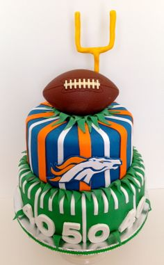 Cakes by Kirsten. Denver Bronco's cake.  Chocolate football and gumpaste accents.  Yellow sourcream cake filled with vanilla buttercream and Godiva truffle buttercream.  #football cake #Denver bronco's cake. #Bronco's