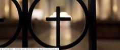 Kreuz im Gitter einer Kirchentür