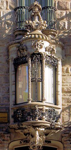 Casa Calvet - Destaca especialmente la tribuna del piso principal, decorada con la inicial del apellido del propietario, un ramo de olivo —símbolo de la paz—, un ciprés —símbolo de hospitalidad— y el escudo de Cataluña; se remata con una cúpula esculpida con dos cornucopias de Amaltea, de la que se esparcen las frutas, y sobre las que se posan dos tórtolas.