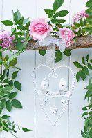 Herzförmiger Metallrahmen mit verziertem Willkommensgruss an Holzstock mit Rosengirlande