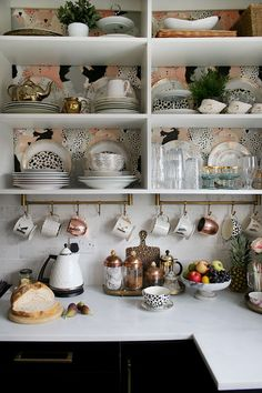 open shelving in kitchen with gold accents and hanging mugs