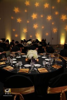 Custom star Gobo lighting projected on a wall during an awards ceremony. Black and gold color theme.