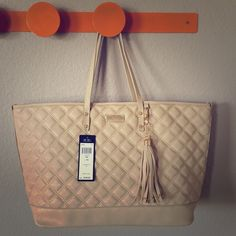 """BCBG tan oversized tote Beautiful bag, quilted look with oversized tassel with studs.  Versatile tan color that goes with everything.  Has a cut (about 1"""") that does not go all the way through, on the bottom of the backside of the bag.  Marked down accordingly.  20"""" wide across top, 11.5"""" tall, base/bottom piece is 15"""" by 5.5"""". BCBG Bags Totes"""