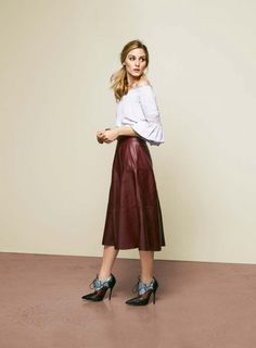 Olivia Palermo wears an off-the-shoulder top, leather skirt, and booties