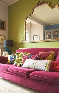 Green wall, pink velvet couch, ornate mirror