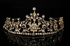 a diamond floral tiara in gold; with a central diamond motif of flower heads, with flanking foliate scrolls.