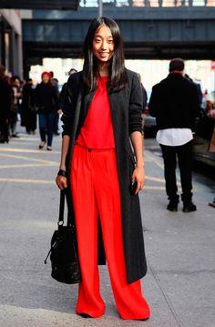 Street style look com macacão vermelho e maxi casaco preto.