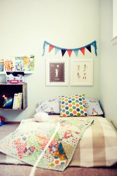 floor beds are cool for multiple reasons! love the polkadot pillow and colorful bunting with the neutral bedspread in this fun kids room