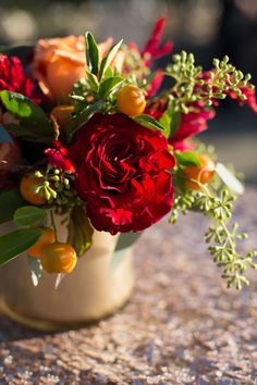 Bright red blooms and mini citrus fruits. Flower arrangement by Petalworks.