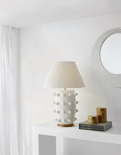 With its repetitious decorative spheres on a beautifully sculpted ceramic base, the Linden Table Lamp by Kelly Wearstler is a playful contrast of both fun and sophistication. The lamp features a linen shade, antique burnished brass detailing, and comes in either a black porcelain or white plaster ceramic finish. Outdoor Wall Lighting, Home Lighting, Decorative Spheres, Media Table, Visual Comfort, City Lights, White Walls, Living Room, Interior Design