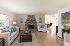 An open floorplan in the living room invites guests and residents in with sunshine and a warm fireplace.