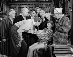Ball of Fire (1941).  Barbara Stanwyck hides out with seven old professors, who all have an amazing library.