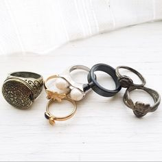 """Seven Ring Bundle. Gold/silver/stone mix + match Seven fun rings. Size varies: two gold tone rings (butterfly and mushroom details) are size 4 but adjustable. All others range from 6-8. The brassy large ring opens up -- you can tuck a photo or keepsake in there. The solid gray ring is made of real hematite stone. Two silver tone rings (hearts and abstract flower detail) have a nice """"distressed"""" darker patina (likely to come off with polishing, but I haven't done so because I enjoy the…"""