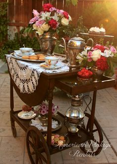 "Tea cart all decked out with the ""Aristocrat Collection"" for a Downton Abbey feel: silver trays, silver pedestal trays, silver coffee servers and tea pots. Silver pitcher, sugar bowl and creamer serve to hold lovely flower arrangements!"