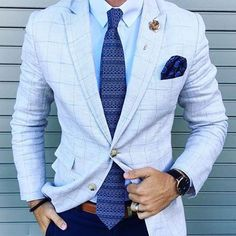 Light grey windowpane check blazer on top of light blue shirt and blue tie.