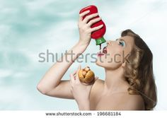 fashion glutton young girl with blonde curly hair eating hot-dog and putting tomato ketchup in her mouth