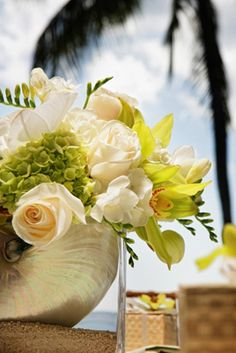 Pearlized nautilus shell resting on beach sand. Adorned with Viburnum, Vendella Roses, Freesia and Green and White Cymbidium Orchids. Simply beautiful! Created by Martin Roberts Design.
