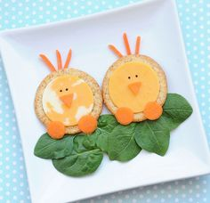chick snacks--round cracker, round cheese slice, carrot pieces, poppy seeds, spinach leaves