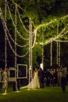 Allestimento di un romantico matrimonio all'aperto in un giardino. Personalizza la tua location con luci a cascata: decorano le piante e illuminano il photo booth