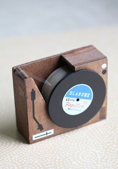 "Put Your Records On Tape Dispenser 21.99 at shopruche.com. This cute record tape dispenser is the perfect retro addition to your desk! In a brown wooden box casing and has a black record in front. Tape included.  Width: 3.5"" x Height: 2.85"""
