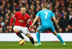 Wayne Rooney of Manchester United is closed down by Sebastian Larsson of Sunderland during the Barclays Premier League match between Manchester United and Sunderland at Old Trafford on February 28, 2015 in Manchester, England.