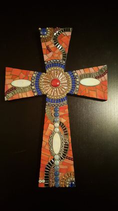 Mosaic Cross Made of all sorts of glass tiles, glass, millifiori, glassnuggets and mirror. On wood. The sides and the back is painted blue.
