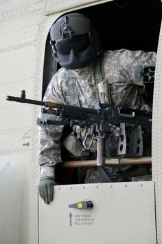 A Boeing CH-47F Chinook crew member looks out the gunner hatch at Camp Humphreys, South Korea, May 14 2014. Soldier with 3rd Battalion, 2nd Aviation Regiment.