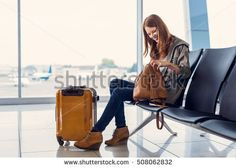 My vacation has just begun. Young smiling woman with yellow suitcase sitting in airport hall while waiting landing