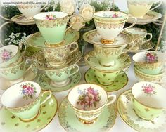 A table full of green teacups adorned with gold and flowers.