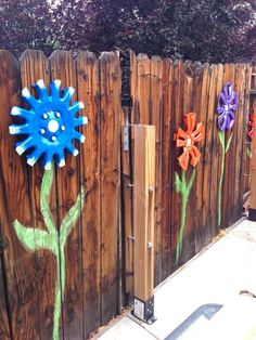 Old hubcaps transformed into flowers, add paint for an amazing fence