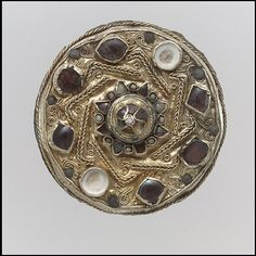 Disk Brooch Date: mid-7th century Culture: Frankish Medium: Gold; garnet; red, pale, amber and blue glass; mother-of-pearl Dimensions: Overall: 1 3/4 x 7/8 in. (4.4 x 2.2 cm) Classification: Metalwork-Gold Credit Line: Gift of J. Pierpont Morgan, 1917 Accession Number: 17.193.83